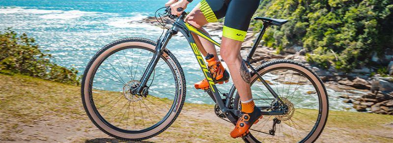 Ciclista andando em mountain bike hardtail subindo montanha próximo ao mar