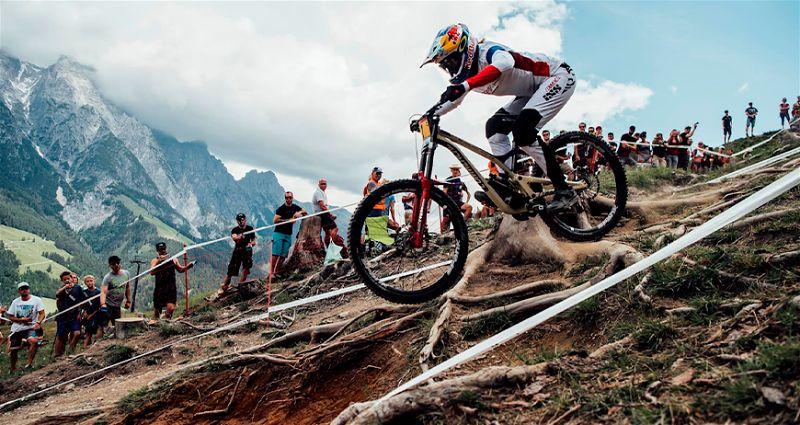Ciclista todo equipado praticando downhill em local montanhoso