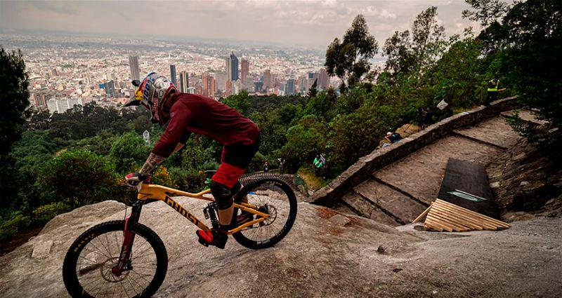 Ciclista praticando downhill em local urbano alto e com escadaria