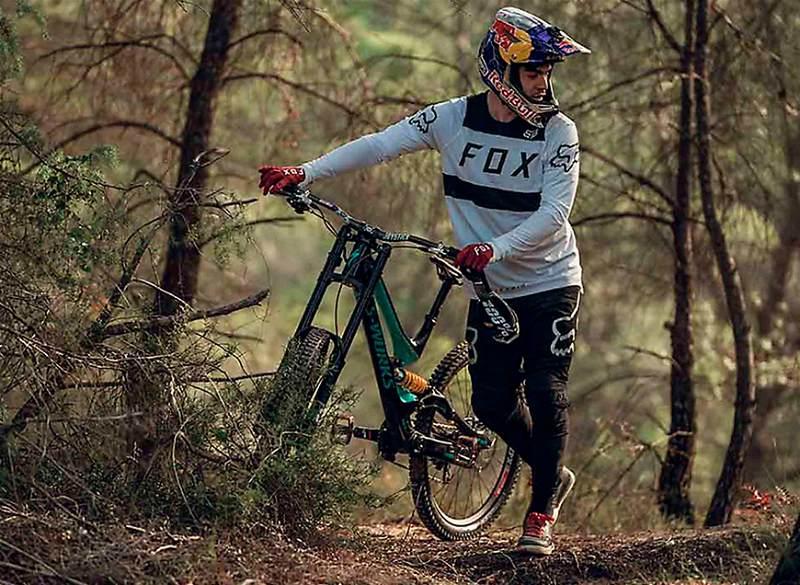 Ciclista em local arborizado segurando sua bicicleta e utilizando os equipamentos para a prática de downhill