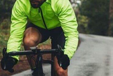Homem pedalando com jaqueta corta vento na chuva