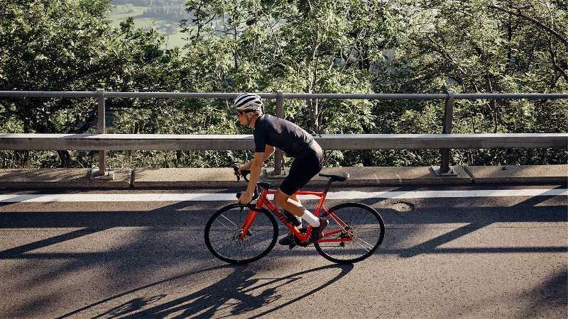 Homem com roupas e acessório de ciclista fotografado de cima em uma ponte andando com uma bicicleta BMC