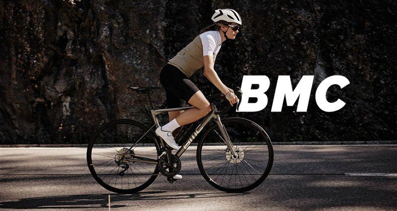 Mulher com roupas e acessórios de ciclista andando em uma bicicleta BMC