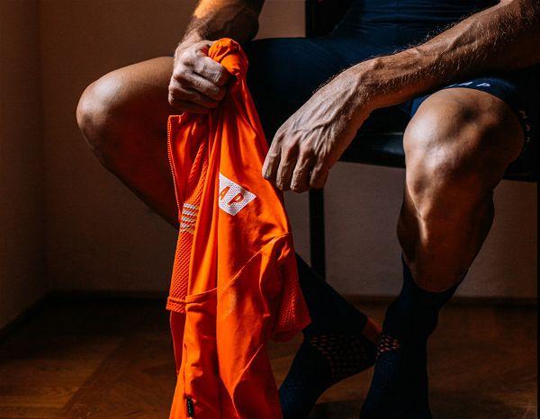 Imagem focada em parte inferior de pessoa sentada em cadeira segurando uma peça de roupa laranja