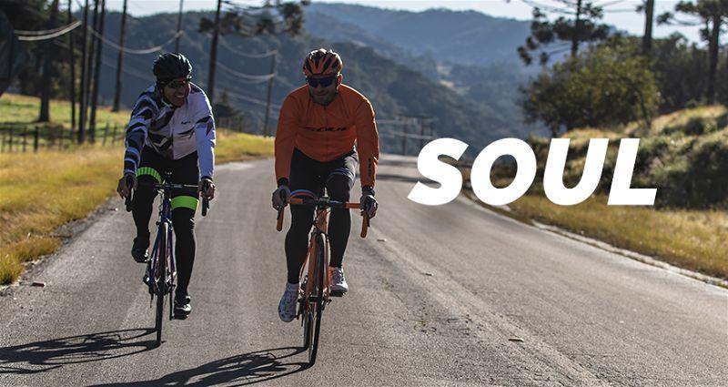 Dois ciclistas em uma estradas andando lado a lado em bicicletas soul