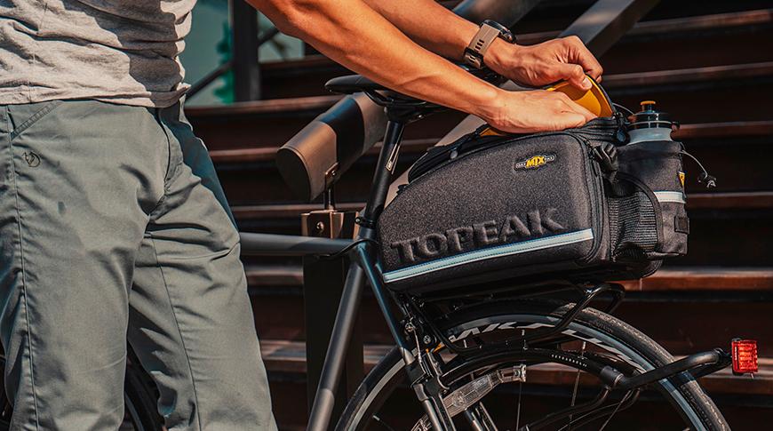 Imagem de uma pessoa utilizando bagageiro em bicicleta em foco