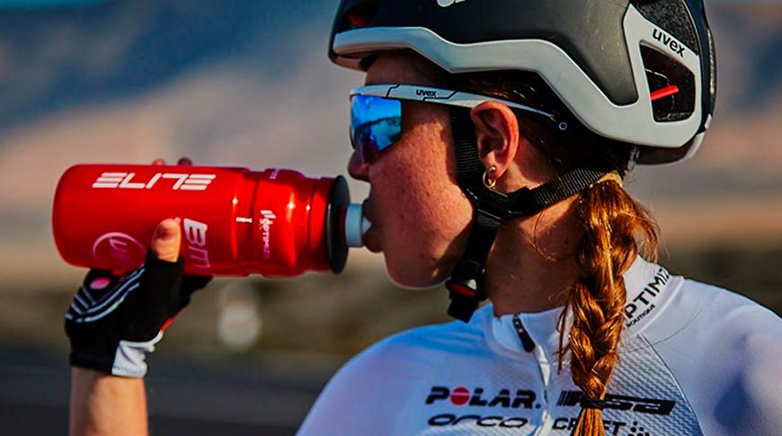 Imagem de uma mulher bebendo agua em garrafa Elite Cycling vermelha