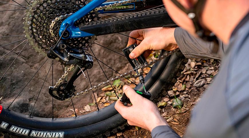 Imagem com uma pessoa utilizando ferramenta multi uso em sua bike na trilha