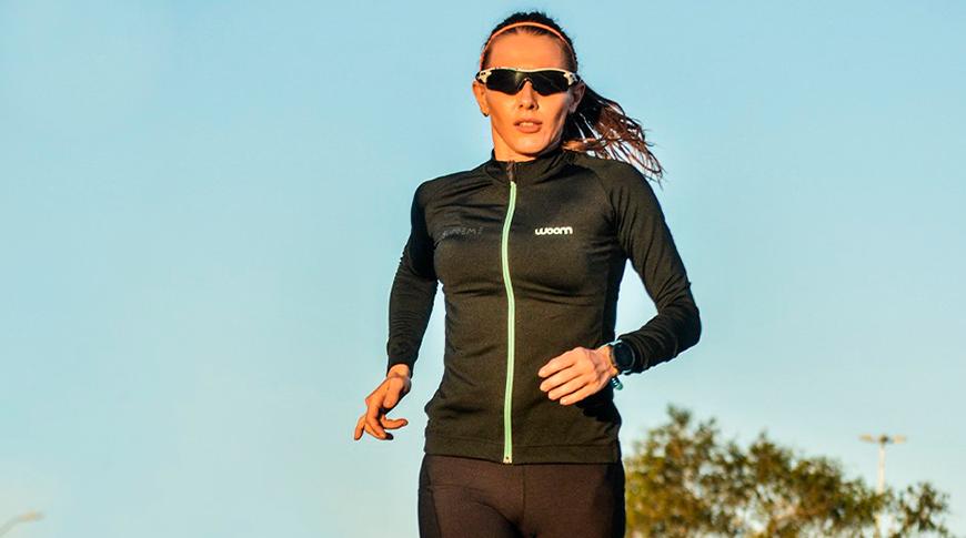 Foto de mulher praticando triatlhon vestindo Woom e óculos Oakley