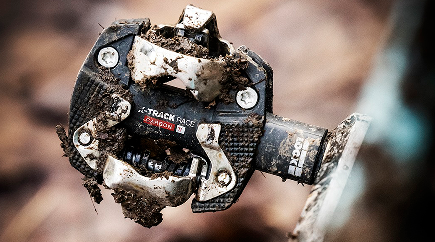 Foto de um pedal clip da marca Look Cycles cheio de lama em foco