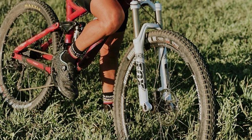 Foto de uma mulher utilizando sapatilha para MTB com foco nas sapatilhas e rodas da bicicleta